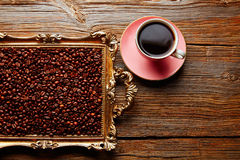 Coffee cup and beans on vintage golden tray. In wooden old table Stock Images