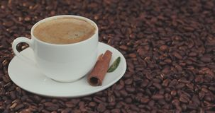 Coffee cup and coffee beans. A white cup of evaporating coffee on the table with roasted bean stock footage