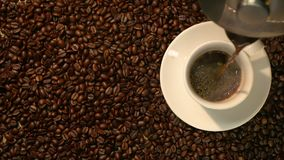 Coffee cup and coffee beans. A white cup of evaporating coffee on the table with roasted bean. Slow Motion coffee pour. stock video footage