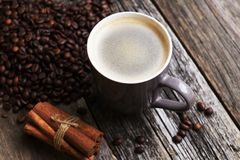 Coffee cup with coffee beans on wood background. Coffee cup with coffee beans and cinnamon on wood background Stock Photography