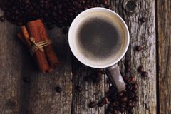 Coffee cup with coffee beans on wood background. Coffee cup with coffee beans and cinnamon on wood background Royalty Free Stock Photos