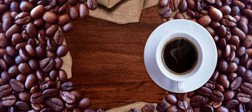 Coffee cup and coffee beans on wood table background vintage style for graphic design. Food and drink stock photography