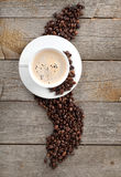 Coffee cup and beans on wooden table Stock Photo