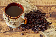 Coffee cup and beans on wooden table background Royalty Free Stock Images