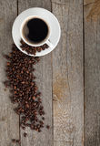 Coffee cup and beans on wooden table Stock Image