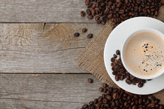 Coffee cup and beans on wooden table Royalty Free Stock Images