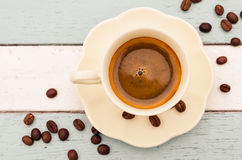Coffee cup and beans on wooden table background Royalty Free Stock Photo