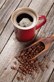 Coffee cup and beans on wooden table Stock Photos