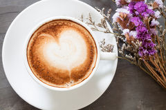 Coffee cup with beautiful violet flower Royalty Free Stock Image