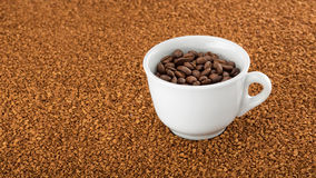 Coffee cup on a bed of instant coffee granules. Stock Photos