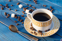 Coffee cup and beens on a table of blue boards Stock Image