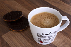 Coffee cup with 2 biscuits aside, wooden background Royalty Free Stock Photography