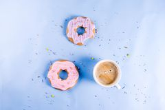 Coffee cup and biscuits donut. Rest and relaxation concept, coffee cup and biscuits donut with sugar coating, with a notepad for notes or wishes on a bright royalty free stock image