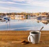 Coffee mug on wood table by harbor Royalty Free Stock Photography