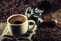 Coffee. Cup of black coffe with coffee beans tamper and portafilter stock photography