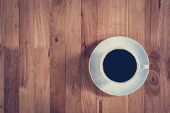 Coffee cup with black coffee on wooden table (top view). Vintage tone Stock Photo