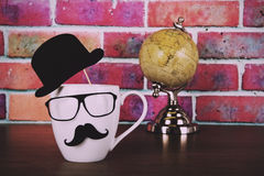 Coffee cup with a black hipster mustache  Vintage Retro Filter. Royalty Free Stock Images