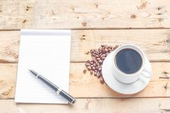 Coffee cup, black pen, notebook on wood table background Royalty Free Stock Photos