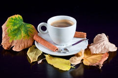 Coffee cup on black wood table with autumn leaves Stock Photography