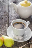 Coffee cup black wooden board brown pears white jug Royalty Free Stock Photos