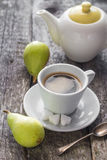 Coffee cup black wooden board brown pears white jug Stock Image