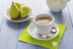 Coffee cup black wooden board brown pears white jug milk Stock Photo