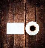 Coffee cup and blank business card on wooden table. White Card f Royalty Free Stock Photo