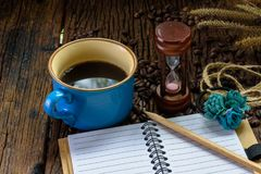 Coffee cup with blank notebook, pencil, hourglass and coffee beans on wooden table Royalty Free Stock Photography