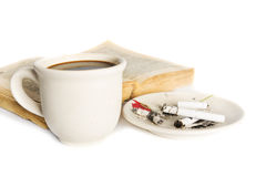Coffee cup with book with cigarettes Stock Photos