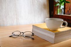 Coffee cup and book with glasses royalty free stock photography