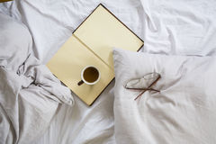 Coffee cup, book, reading glasses on bed Royalty Free Stock Images