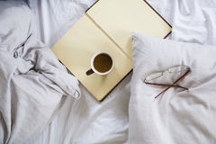 Coffee cup, book, reading glasses on bed Stock Images