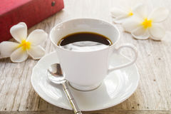 Coffee cup and book on wooden table Stock Photos