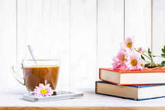 Coffee cup and books or journal with flowers. Stock Photos