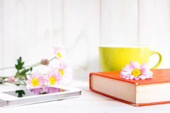 Coffee cup and books or journal with flowers. Coffee cup and books or journal with flowers arranged on a neutral white painted desk Stock Photos