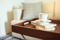 Coffee cup Books on table wooden tray Pillow on sofa Home Interior. Leisure lifestyle Stock Photo