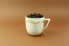 Coffee cup with a bow and coffee beans brown background.  Royalty Free Stock Image