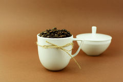 Coffee cup with a bow and coffee beans with sugar bowl Royalty Free Stock Photo