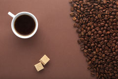 Coffee cup,brown sugar and beans on a brown Royalty Free Stock Photo