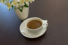 The coffee Cup on a brown table. White coffee Cup on a brown table with white vase Royalty Free Stock Images