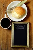 Coffee cup and bun with butter, slate chalk board Stock Images