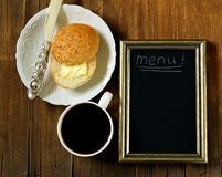 Coffee cup and bun with butter, slate chalk board Royalty Free Stock Image