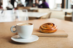 Coffee cup and bun with cinnamon in cafe Royalty Free Stock Photos