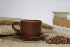 Coffee cup on burlac with book and blur background stock images