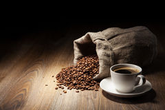 Coffee cup with burlap sack of roasted beans Royalty Free Stock Photos