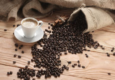 Coffee cup with burlap sack of roasted beans Royalty Free Stock Photography