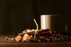 Coffee cup with burlap sack of roasted beans on rustic table Royalty Free Stock Photos