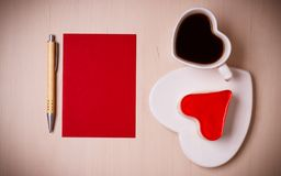 Coffee cup cake in heart form and blank paper. Coffee cup jelly cake in form of heart and red paper blank with pen on wooden surface, top view copy space for royalty free stock photo