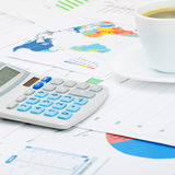 Coffee cup and calculator over different charts - close up shot Stock Photography