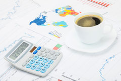 Coffee cup and calculator over financial charts stock photography